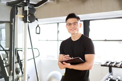 トレーニングジムで笑顔で立つアジア人男性トレーナー