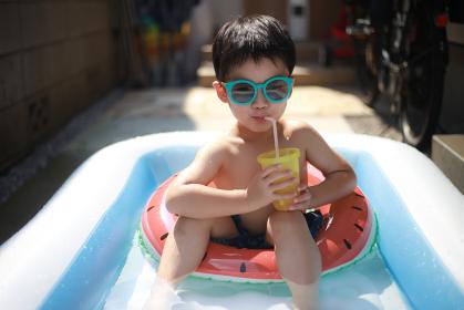 プールで飲み物を飲む男の子
