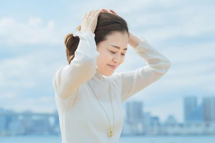 両手で髪を整える女性