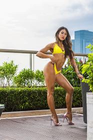 Beautiful young woman posing in yellow bikini in Bangkok