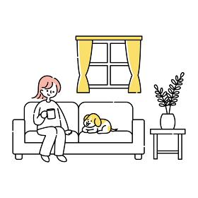 リビングのソファーに座って犬と一緒にくつろ