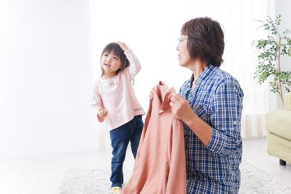 洗濯物をたたむおばあさんと子ども