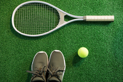 Close up of racket with shoes and tennis ball