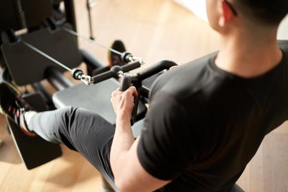 ロープーリーマシンでトレーニングをするアジア人男性
