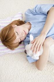 寝転がりながらフレンチブルドッグを抱き寄せる笑顔の女性