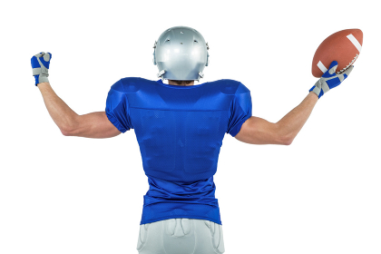 Rear view of American football player holding ball