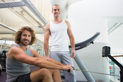 Male trainer assisting man on fitness machine at gym