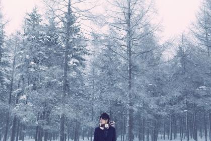 雪が積もった森に立つ日本人男性