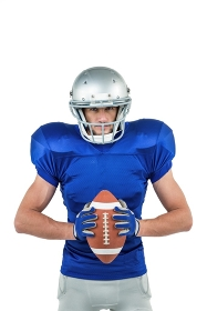 Portrait of confident American football player holding ball