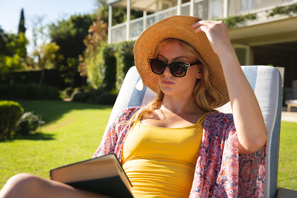 Caucasian woman wearing sunhat and sunglasses relaxing in sunny garden holding book. spending free time at home.