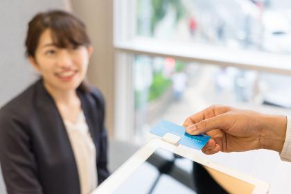 タブレット端末でクレジットカードの決済をする女性