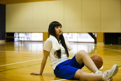 体育館の床に座る女の子