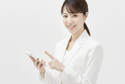 スマートフォンを持つ、白いスーツ姿の女性