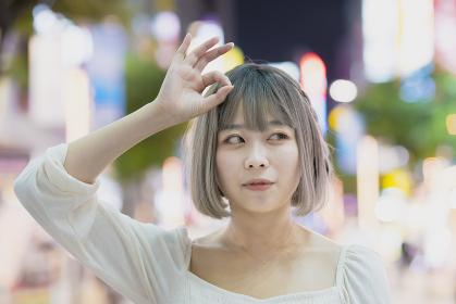 夜の繁華街で、OKサインをする女性