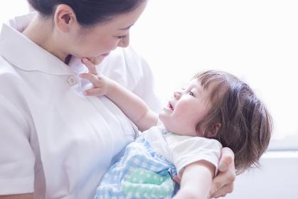 子供を抱っこする看護士