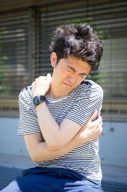 屋外で肩をストレッチする男性