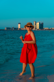Woman in red dress waking along the beach and enjoing life