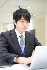 真剣な表情で仕事をする会社員(男性・電話・パソコン)