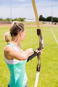 Happy female athlete practicing archery