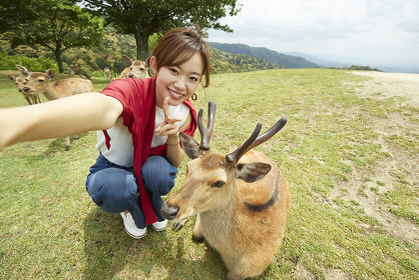 奈良公園で鹿と自撮りする日本人女性