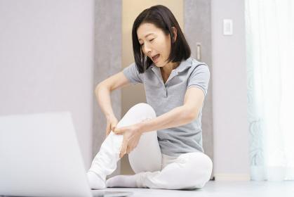 パソコンを見ながら軽い運動をして、苦しい表情をする女性