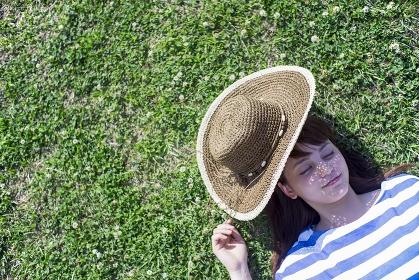 草原で仰向けに寝る日本人女性