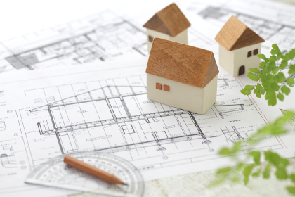 家の模型とマイホームの設計図のイメージ