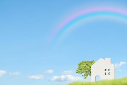 虹がかかった青空の背景に緑と白い家