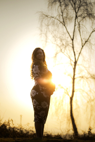 A pregnant female with red hair stood in front of a tree and sunset