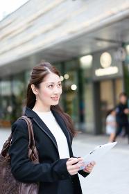 屋外でモバイル端末を持って仕事をする女性