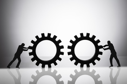 Silhouette Of Two Businesspeople Joining Gears