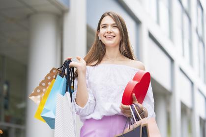 たくさんの買い物袋を抱える女性