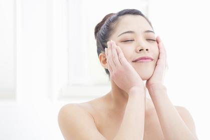 顔をマッサージする女性