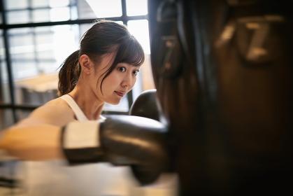 トレーニングジムでキックボクシングをするアジア人女性