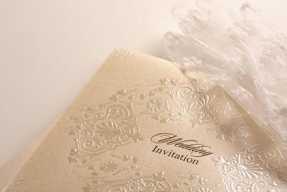 結婚式の招待状と新婦のレースの白い手袋