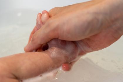 沐浴で新生児の足を洗う
