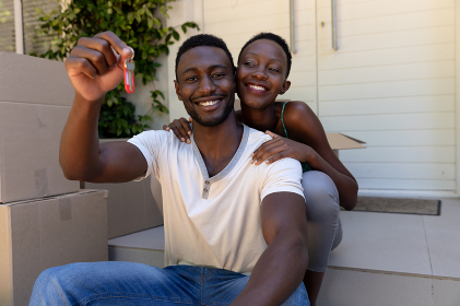 Portrait of african american couple moving house holding keys and smiling. staying at home in isolation during quarantine lockdown.
