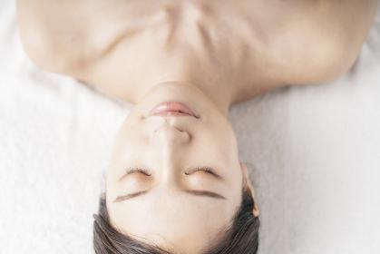 エステサロンで横になる若い女性のリラックスした顔