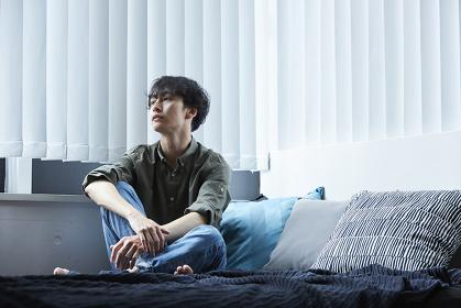 ベッドの上でくつろぐ日本人男性