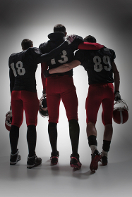 The three american football players on gray background