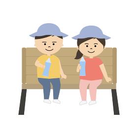 椅子に座って水分補給をする男の子と女の子のイラスト