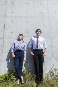 コンクリートの壁の前に立つ男女