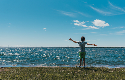 Boy standing on the shoreline of a lake on a sunny summer day. , Kingston, ON, Canada