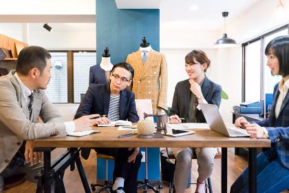 オフィスでミーティングする男女(アパレル・ブランド・ファッション)