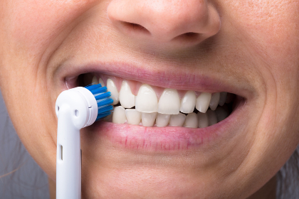 Woman's Teeth With Electrical Toothbrush