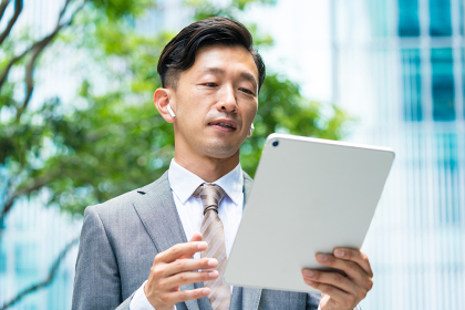 タブレットPCの画面を見るビジネスマン