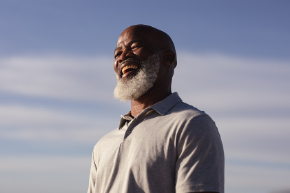 Senior african american man smiling while standing on the beach. travel vacation retirement lifestyle concept