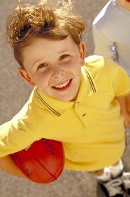 Portrait, Ganzfigur, froehliecher sommersprossiger Junge mit braunen Haaren bekleidet mit gelbem T-Shirt im Alter von 6 Jahren auf der Strasse mit orangem Rugby Ball unter dem Arm