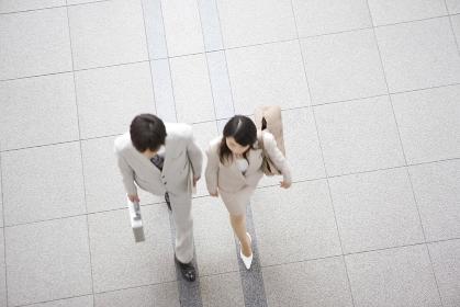 歩くビジネスマンとビジネスレディ俯瞰
