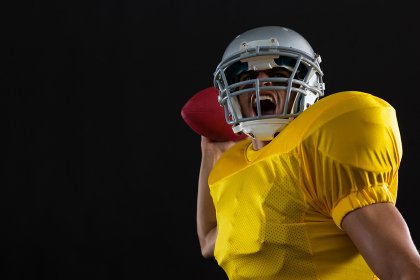 Energetic American football player holding a ball in one hand